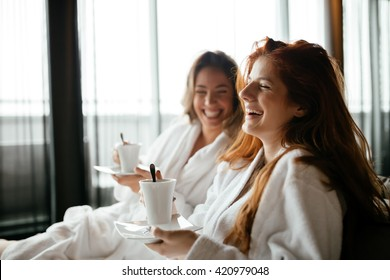 Women in bathrobes enjoying tea during wellness weekend