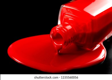 Women beauty products, luxury fashion and makeup concept with close up on a dropped bottle of red nail polish sitting in a pool of spilled red liquid on black background with dramatic lighting