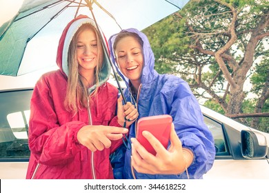 Women best friends enjoying with smartphone with sun coming out after the rain - Car trip with young girlfriends having fun together - Vintage filtered look with soft focus on faces and sunshine halo