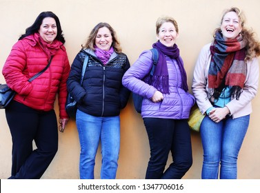 Women best friends smiling and walking at the city.  Outdoors lifestyle fashion portrait. Positive emotions.