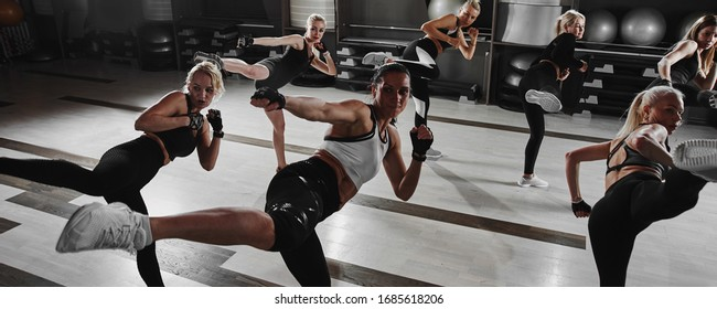 Women in black and white sportswear on a real group workout in the gym train to fight, kickboxing with a trainer