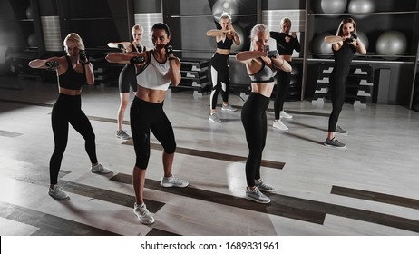 Women in black and white sportswear on a real group body Combat workout in the gym train to fight, kickboxing with a trainer
