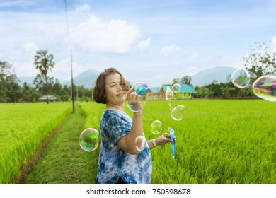 Women are blowing bubbles in a rice field in a bright atmosphere.
