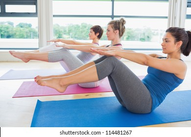 Women in boat pose in yoga class in fitness studio