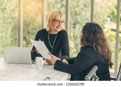 Women boss and consult with the secretary woman of work and check the minutes or report or official document, at meeting room.