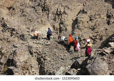 Women bring their food and drink needs through rugged mountain roads because of  Al-Houthi militia siege of the villages of Jabal Habashi District in the  west of Taiz City,Yemen.