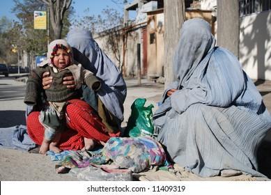 Women in burka begging
