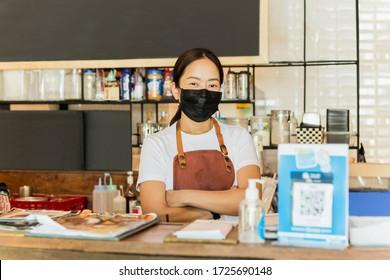 Les femmes propriétaires de cafés portant un masque de protection se tiennent dans le contre-Convid-19 conceptuel.
