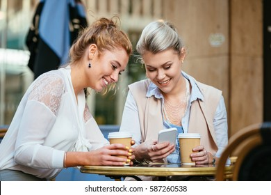 Women at a cafe with their smart phones