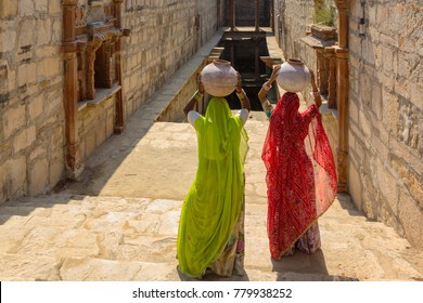 Women carry ceramic pot in the step well