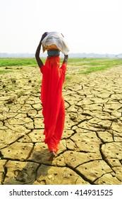 Frauen, die Körbe auf trockenem Boden tragen, Indien