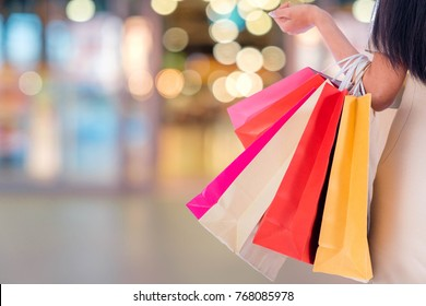 Women carrying a lot of colorful shopping bags in blurred shopping mall