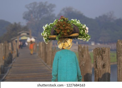 A women carrying a flat round basket with goods on her head walking across U Bein Bridge in Amarapura, Mandalay, Myanmar. The women is near the foreground.
