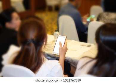 Women carrying a phone or hand holding Mobile phone In the meeting room. with blank copy space screen for your advertising text message or promotional content. For Graphic display montage.