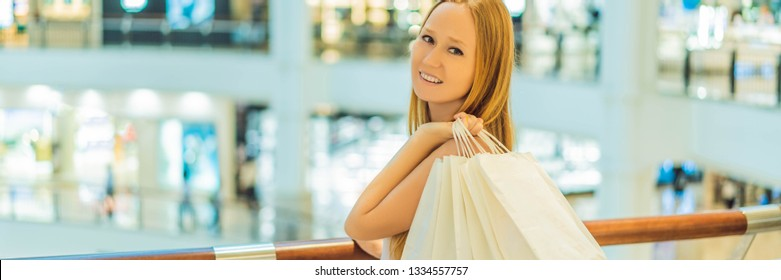 Women carrying a lot of shopping bags in blurred shopping mall BANNER, LONG FORMAT