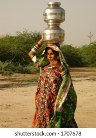 a women carrying utensil on her head