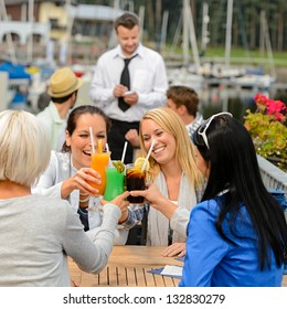 Women celebrating with cocktails at harbor restaurant