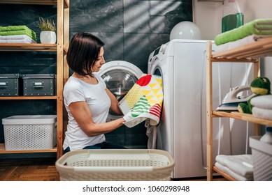Women checking her laundry as she removes them from the washing machine.