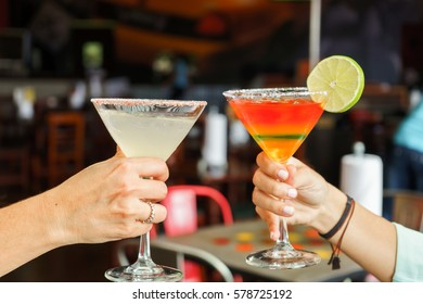 women cheering a cocktails, margarita with lemon and mojito.