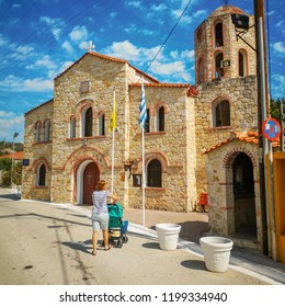 women and child in stroller going to a stone medieval church in greece, greece flag