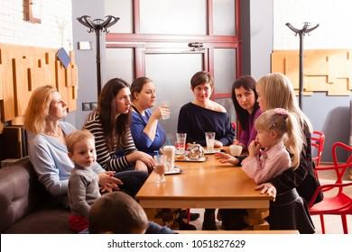 Women and children having a drink