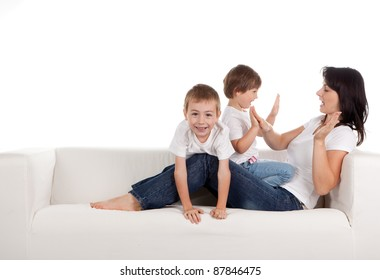 Women and children lying on a white sofa.  White background