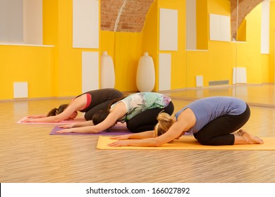 Women in child's pose in yoga class in fitness studio