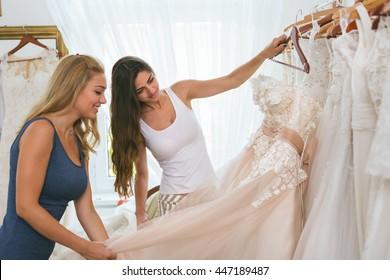 Women choosing wedding dress in shop