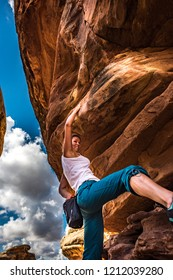 Women Climber practicing bouldering on a beautiful red rock in Canyonlands Utah USA