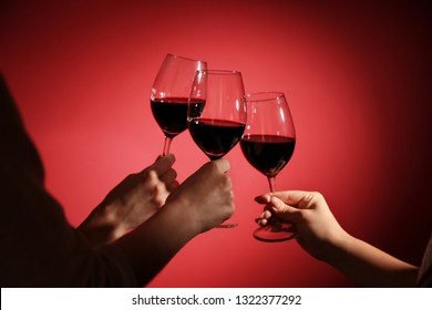 Women clinking glasses with tasty red wine on color background