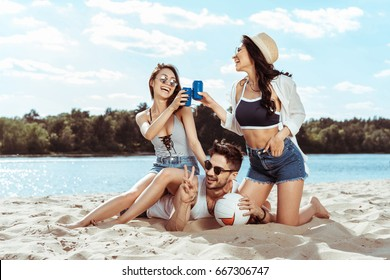 women clinking soda drinks while sitting on man's back on beach