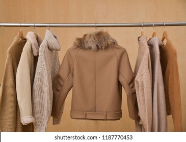 Women coat and fur jacket with sweater on hangers isolated wooden background