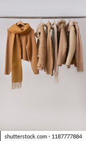 Women coat and fur jacket with sweater with scarf on hangers isolated