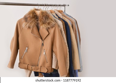 Women coat and fur jacket with sweater on hangers isolated