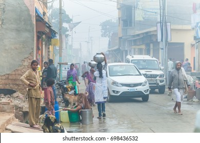Women collect water in a plastic container in the morning on the street.India, Govardhan, November 2016