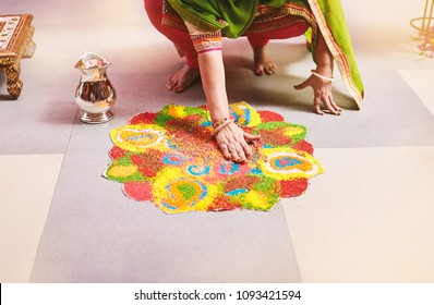 Women coloring tradition colorful rice art or sand art (Rangoli) on the floor with paper pattern using dry rice and dry flour with colored from natural pigments like sindoor, haldi (turmeric)
