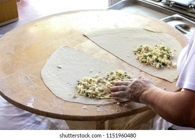 Women cooks turkish pita 'gozleme' with cheese and greens
