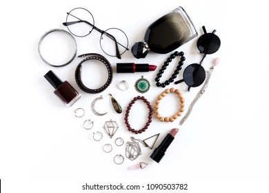 Women cosmetics and accessories lined with heart shape on a white background