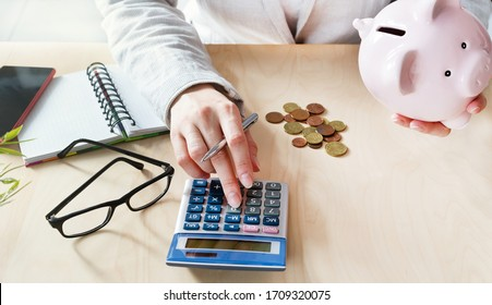 Women counting coins on calculator taking from the piggy bank. Use last savings, unemployment and bankruptcy concept. Crisis and dismissal.