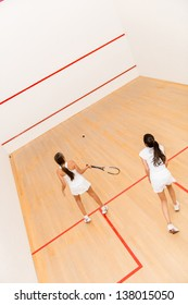 Women at the court playing a match of squash