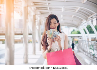 Women crazy shopaholic holding shopping bags , money ,credit card person at shopping malls.Fashionable Woman love online website with sales tag on black friday. E-commerce digital marketing lifestyle