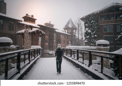 Women crossing the bridge in Mammoth Lakes Village during a snow storm in winter.
