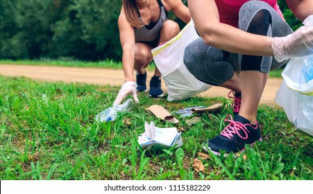 Women crouching with bag picking up trash doing plogging
