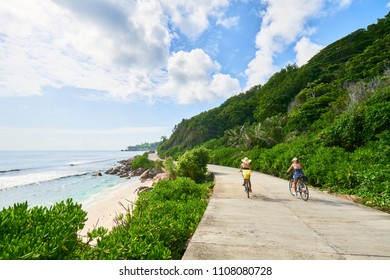 women cycling around the beautiful beaches, La Digue Island, Seychelles