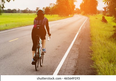 Women cycling on the road morning day - sport bike concept