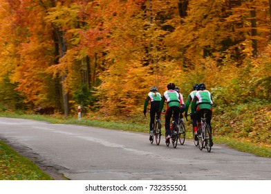 women cycling workout on autumn road in forest