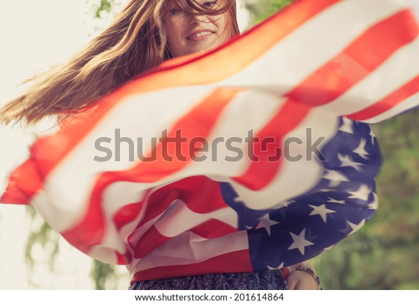 Women dancing with US flag blurred motion shot toned image
