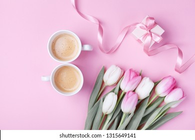 Women day 8 March concept. Morning coffee, gift box and spring tulip flowers on pink pastel background. Flat lay.