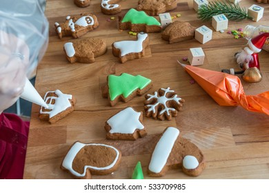 Women decorates christmas cookie in the shape of house. Some cookies are decorated. Wooden background