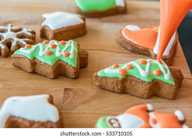 Women decorates christmas cookie in the shape of Christmas Tree. Some cookies are decorated. Wooden background